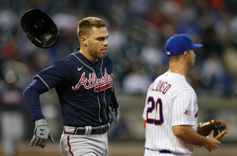 Atlanta Braves first baseman Freddie Freeman, left, loses his helmet running to first base against the New York Mets during the fourth inning of a baseball game Wednesday, June 23, 2021, in New York. (AP Photo/Noah K. Murray)