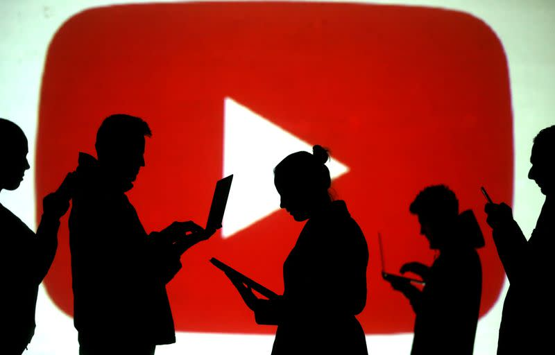 FILE PHOTO: Silhouettes of laptop and mobile device users next to a screen projection of the YouTube logo in this picture illustration