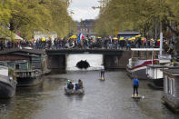 Protestors holding yellow umbrellas and the Dutch flag cross Prinsengracht canal during a demonstration against coronavirus related restrictions in Amsterdam, Netherlands, Sunday, May 2, 2021. (AP Photo/Peter Dejong)