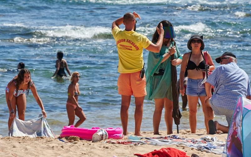 The social distancing police make their rounds on a Portuguese beach - getty