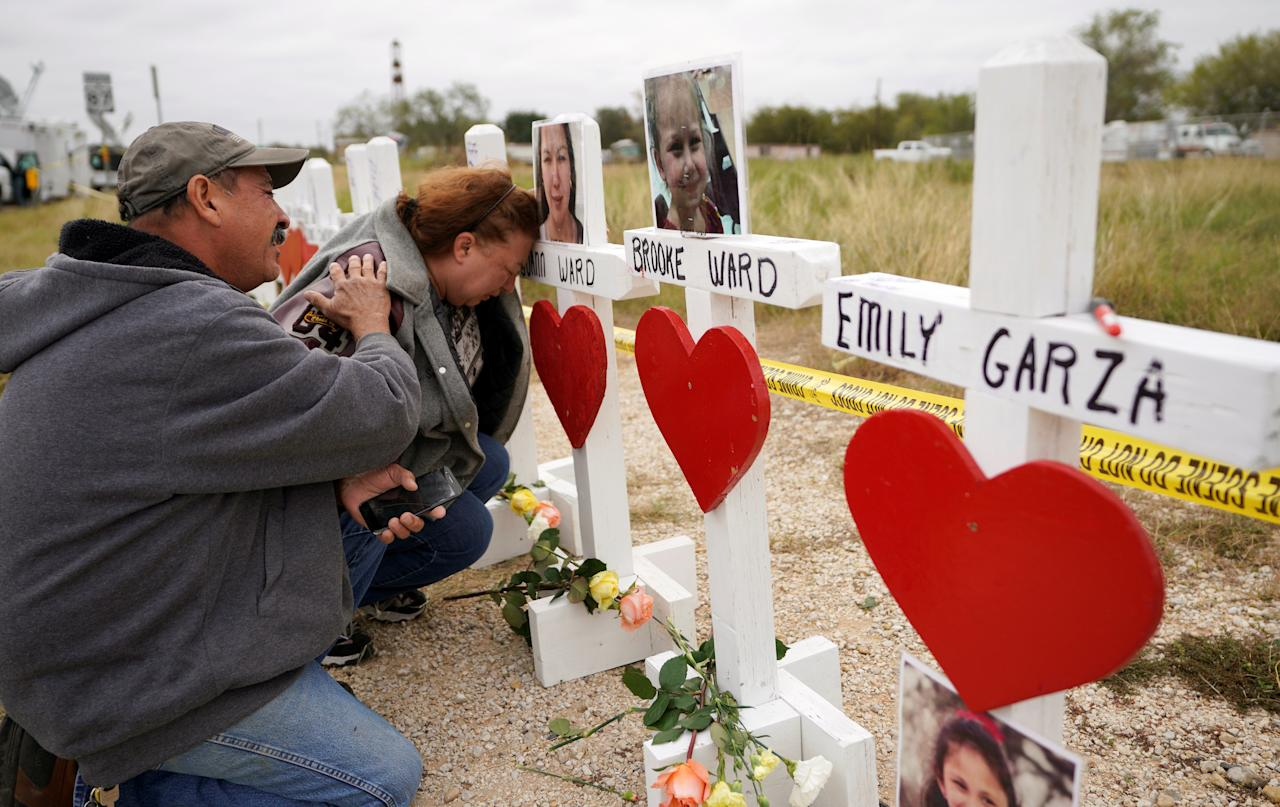 <p>Lorenzo Flores (L) and Terrie Smith react at a line of crosses in remembrance of those killed in the shooting at the First Baptist Church of Sutherland Springs, Texas, Nov. 9, 2017. (Photo: Rick Wilking/Reuters) </p>