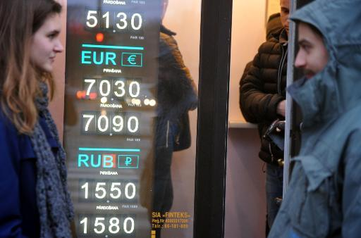 <p>People walk past a currency exchange office in Riga, Latvia on December 27, 2013</p>