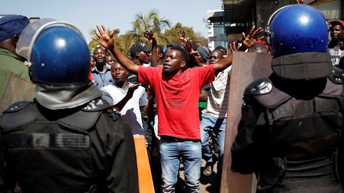 A supporter of the Movement for Democratic Change (MDC) opposition party of Nelson Chamisa gestures to the riot police as they march on the streets of Harare, 1 August 2018