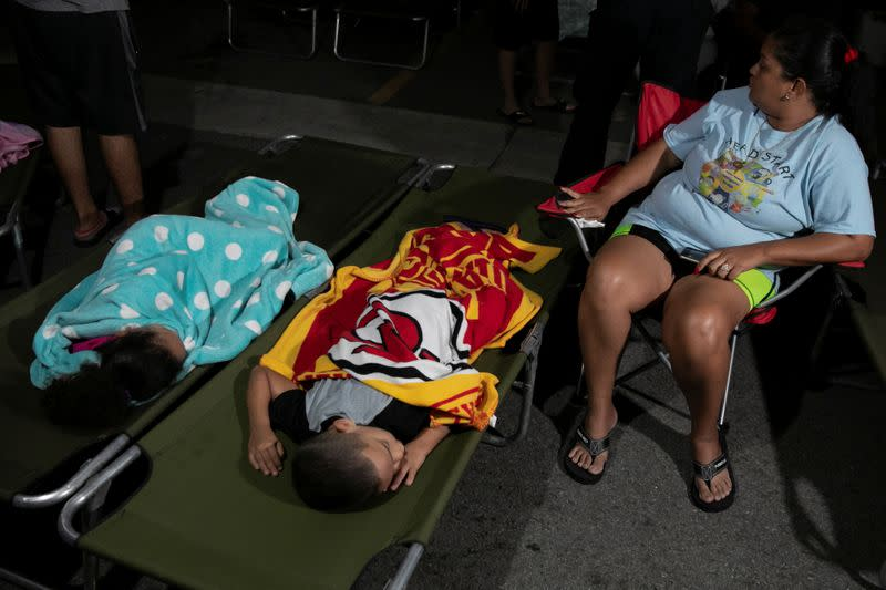 People rest at a makeshift camp outside their apartment building after an earthquake in Yauco