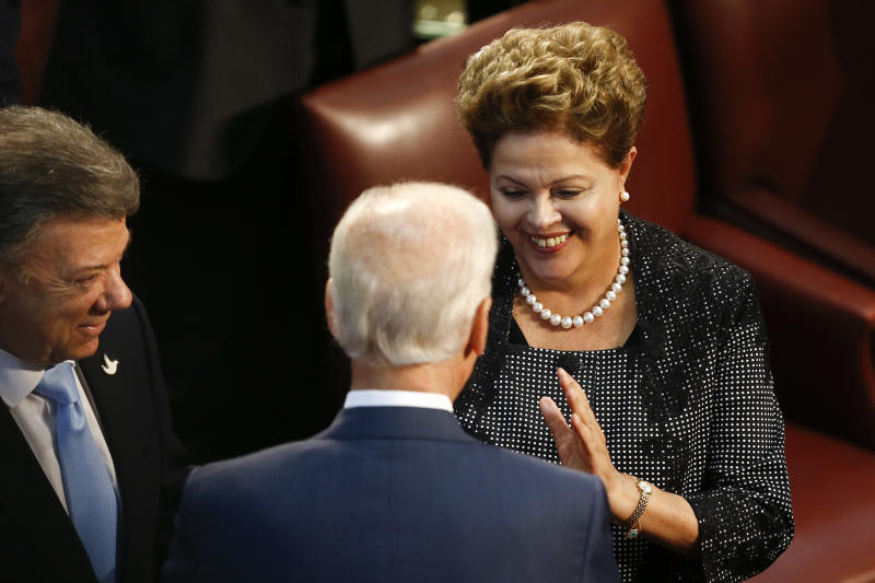Brazilian President Dilma Rousseff, right, talks with Vice President Joe Biden embrace as Colombian President Juan Manuel Santos watches, before the start of Michelle Bachelet's swearing-in ceremony as Chile's president, in the Chilean Congress in Valparaiso, Chile, Tuesday, March 11, 2014. (AP Photo/Victor R. Caivano)