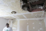 **HOLD FOR MOVEMENT WITH STORY BY JUAN LOZANO**Houston resident Lawrence Hester looks at a hole in the ceiling Thursday, January 16, 2020, of his daughter's bedroom that was caused by a leaky roof damaged during Hurricane Harvey in 2017. Hester said he was unable to get help from a city program created to fix homes damaged during Harvey and had to endure hazardous living conditions for more than two years. He turned to a local nonprofit to fix his home. The city program has finished rebuilding less than 70 homes since beginning in January 2019. (AP Photo/Juan Lozano)