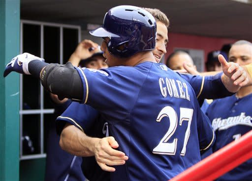 Milwaukee Brewers' Carlos Gomez (27) is hugged by Ryan Braun after hitting a solo home run in third inning of a baseball game against the Cincinnati Reds, Thursday, Sept. 27, 2012, in Cincinnati. (AP Photo/Al Behrman)