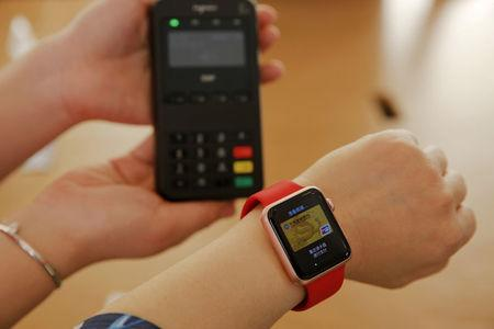 FILE PHOTO : An employee uses an Apple Watch to demonstrate to reporters how to pay using the Apple Pay service at an Apple store in Beijing