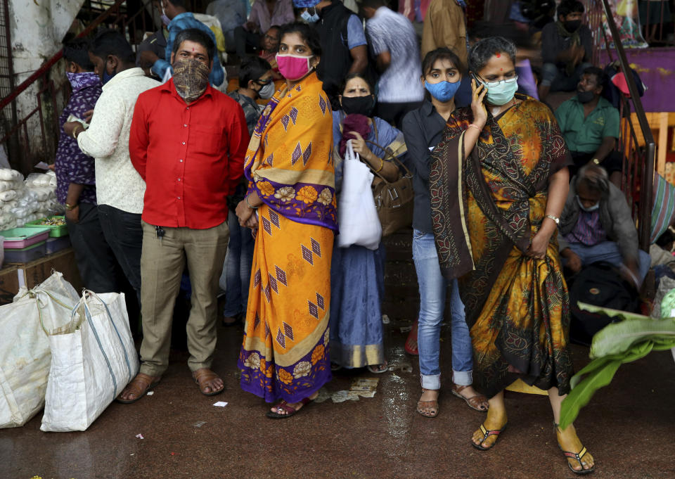 People wait to leave as it rains after shopping at a wholesale flower market ahead of the Hindu festival of Dussehra, in Bengaluru, India, Friday, Oct. 23, 2020. Weeks after India fully opened up from a harsh lockdown and began to modestly turn a corner by cutting new infections by near half, a Hindu festival season is raising fears that the disease could spoil the hard-won gains. Health experts worry the festivals can set off a whole new cascade of infections, further testing and straining India's battered health care system. (AP Photo/Aijaz Rahi)
