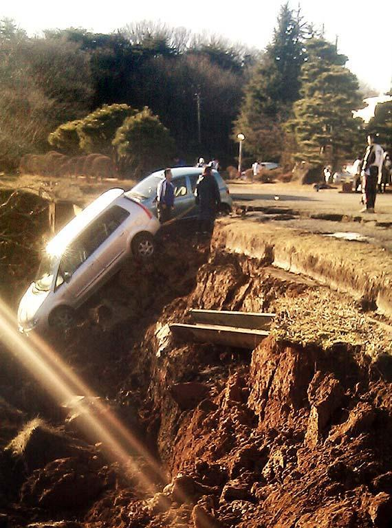 Vehicles are crushed by a collapsed road at a carpark in Yabuki, in southern Fukushima Prefecture on March 11, 2011 after an earthquake rocked Japan. A massive 8.9-magnitude earthquake hit Japan unleashing a monster 10-metre high tsunami that sent ships crashing into the shore and carried cars through the streets of coastal towns. AFP PHOTO