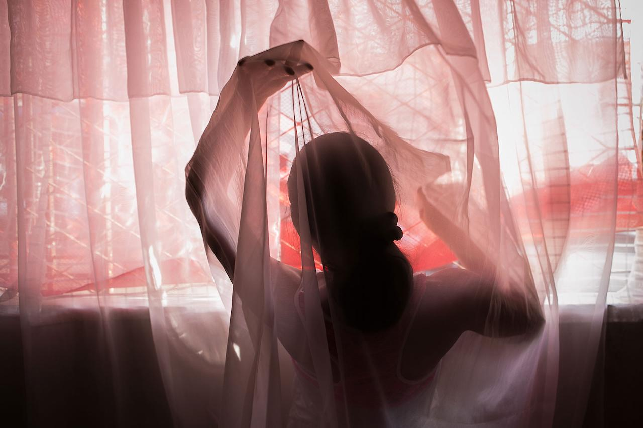 <p>Marilyn, Angel's mother, through the curtains in her house in San Cristóbal, Venezuela, close to the Colombian border. (Photo: Fabiola Ferrero) </p>