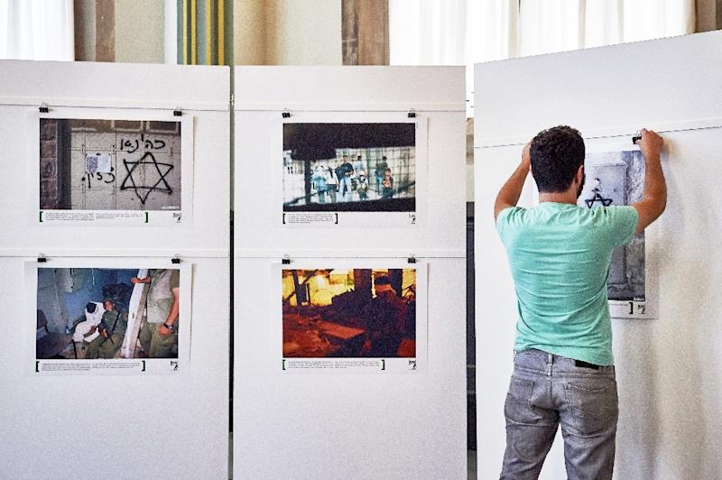 "Alon Sahar, a former Israeli soldier displays photographs at an exhibition of the Israeli NGO ""Breaking the Silence"" at the Kulturhaus Helferei on June 3, 2015 in Zurich (AFP Photo/Michael Buholzer)"