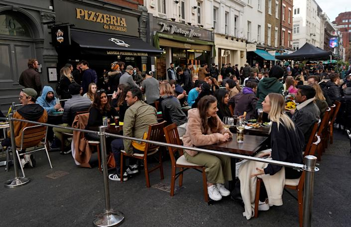 People drink in the street in the Soho area of London, on April 16, 2021 following step two of the government's roadmap out of England's third national lockdown. - Britons on Apri l12 toasted a significant easing of coronavirus restrictions, with early morning pints -- and much-needed haircuts -- as the country took a tentative step towards the resumption of normal life. Businesses including non-essential retail, gyms, salons and outdoor hospitality were all able to open for the first time in months in the second step of the government's roadmap out of lockdown. (Photo by Niklas HALLE'N / AFP) (Photo by NIKLAS HALLE'N/AFP via Getty Images)