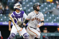San Francisco Giants' Brandon Belt, front, follows the flight of his two-run home run with Colorado Rockies catcher Elias Diaz in the first inning of game two of a baseball doubleheader Tuesday, May 4, 2021, in Denver. (AP Photo/David Zalubowski)