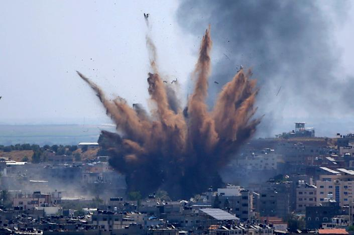 Smoke rises following Israeli airstrikes on a building in Gaza City in May (AP)