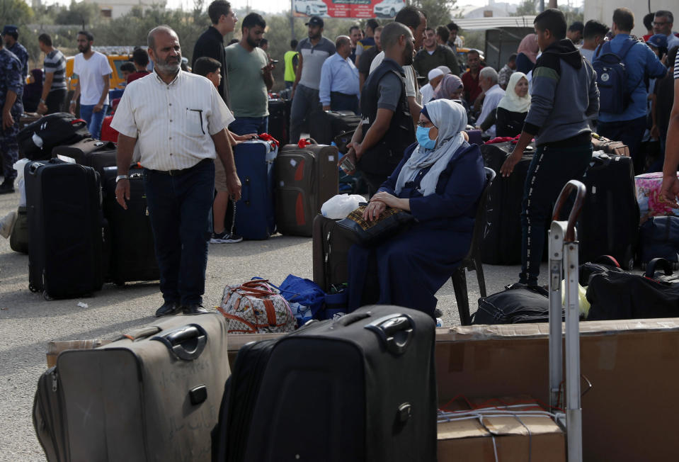 Passengers sit next to their luggage as they wait to cross the border to the Egyptian side of Rafah crossing, in Rafah, Gaza Strip, Tuesday, Aug. 11, 2020. Egypt reopened Rafah Crossing for three days starting Tuesday for humanitarian cases in and out of the Gaza Strip, including medical patients and people who had Egyptian and international citizenship. The border was closed since March. (AP Photo/Adel Hana)