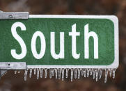 Ice clings to a highway sign along N.C. Hwy 66 South in Kernersville, N.C., as the Triad area experienced a light case of freezing rain, Wednesday, Dec. 16, 2020 (Walt Unks/The Winston-Salem Journal via AP)
