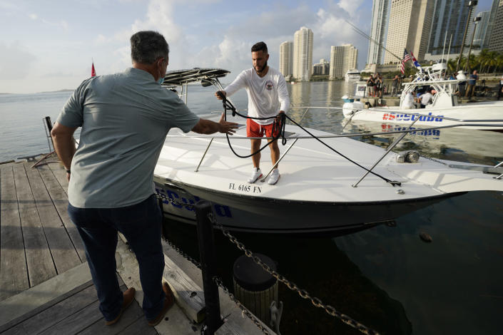 Ramon Saul Sanchez, left, leader of the nonprofit group Movimiento Democracia that launched several flotillas in the past, helps boater Julio Gonzalez tie up his boat, Friday, July 23, 2021, in downtown Miami. A small group of Cuban Americans launched motorboats from Miami to their homeland to show support for people experiencing hardships on the island. Five boats left the Bayside marina just before 8 a.m. Friday. They plan to refuel in Key West before heading into the Florida Straits. (AP Photo/Wilfredo Lee)