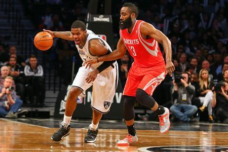 Apr 1, 2014; Brooklyn, NY, USA; Brooklyn Nets guard Joe Johnson (7) drives to the net past Houston Rockets guard James Harden (13) during the fourth quarter at Barclays Center. The Nets defeated the Rockets 105-96. Mandatory Credit: Ed Mulholland-USA TODAY Sports