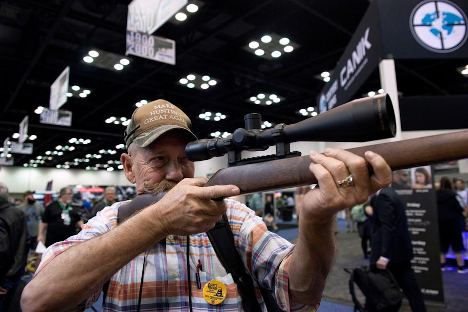 <p>Mark McKenzie of Tulsa, Oklahoma, looks through the scope of a deactivated rifle at the 2019 National Rifle Association (NRA) Annual Meetings and Exhibits in Indianapolis, Indiana, on April 26, 2019. </p> ((Photo by SETH HERALD/AFP via Getty Images))