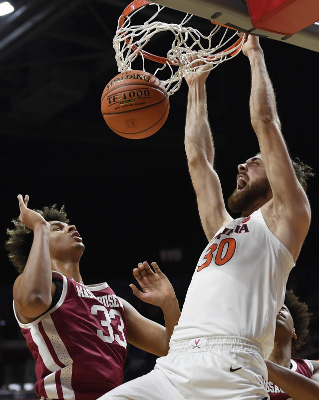 Virginia's Jay Huff, right, dunks over Massachusetts' Tre Mitchell during the second half of an NCAA college basketball game, Saturday, Nov. 23, 2019, in Uncasville, Conn. (AP Photo/Jessica Hill)