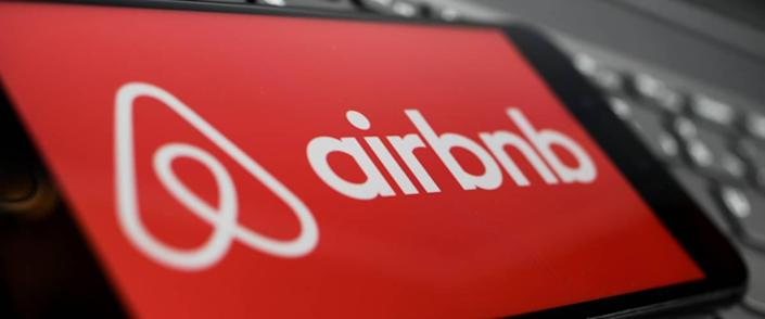 Close up of isolated mobile phone with red airbnb logo lettering on computer keyboard