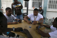 Tenants play dominoes outside an apartment building at the Imperial Courts housing project in the Watts neighborhood of Los Angeles, Wednesday, June 17, 2020. (AP Photo/Jae C. Hong)