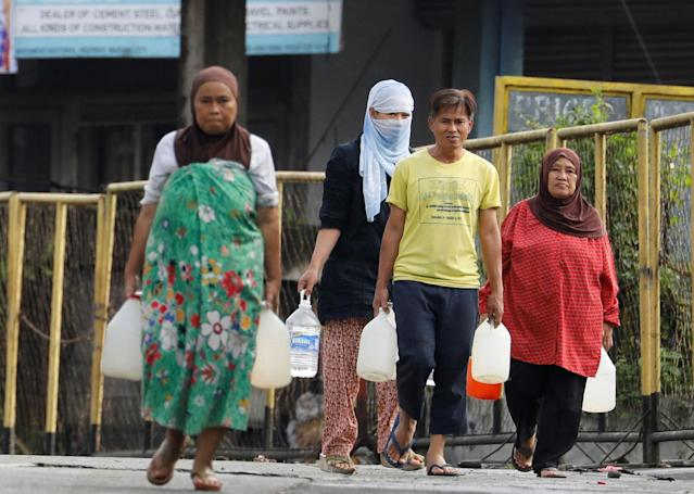<p>Residents who were displaced due to fighting between government soldiers and the Maute militant group, carry plastic containers of water in Marawi City in southern Philippines May 28, 2017. (Erik De Castro/Reuters) </p>