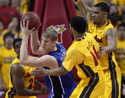 Duke forward Miles Plumlee, center, looks for a teammate as he is guarded by Maryland's Pe'Shon Howard, left, Sean Mosley, second from right, and Ashton Pankey, right, in the first half of an NCAA college basketball game in College Park, Md., Wednesday, Jan. 25, 2012. (AP Photo/Patrick Semansky)