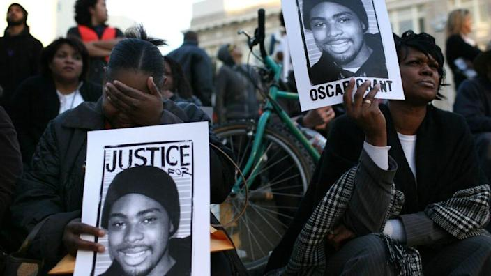 This January 2009 photo shows protesters with signs picturing slain 22-year-old Oscar Grant III, who was shot in the back by a Bay Area Rapid Transit police officer as he lay face down on the ground, during a demonstration at Oakland City Hall. (Photo by Justin Sullivan/Getty Images)