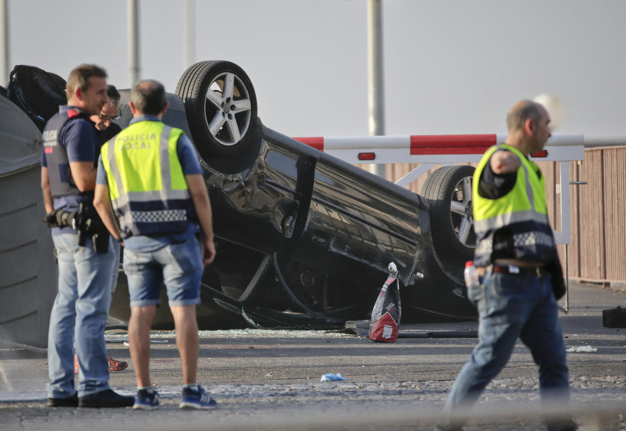 <p>Police officers walk near an overturned car onto a platform at the spot where terrorists were intercepted by police in Cambrils, Spain, Friday, Aug. 18, 2017. The police force for Spain's Catalonia region says the five suspects shot and killed in the resort town of Cambrils were carrying bomb belts, which have been detonated by the force's bomb squad. (Photo: Emilio Morenatti/AP) </p>