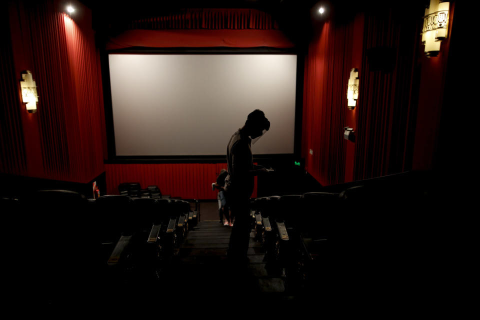 An usher looks for seats at a cinema after almost a year of theaters being closed due to the COVID-19 pandemic, in Buenos Aires, Argentina, Wednesday, March 3, 2021. (AP Photo/Natacha Pisarenko)