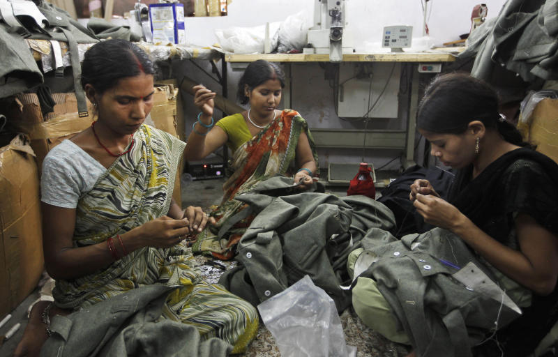In this, June 2, 2012 photograph, workers sew dresses being prepared for a reenactment of World war II at a workshop owned by Indian businessman Ashok Rai, unseen, in Sahibabad, India. From Hollywood war movies to Japanese Samurai films to battle re-enactments across Europe, Rai is one of the world's go-to men for historic weapons and battle attire. (AP Photo/Saurabh Das)