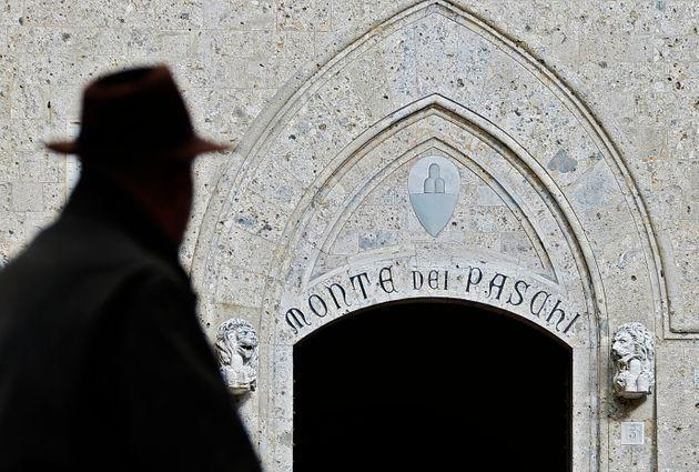 A man walks on January 25, 2013 past the headquarters of the Banca Monte dei Paschi di Siena (MPS), the world's oldest bank to adopt a government aid plan amid revelations of a derivatives scandal. A media report on January 22 that said BMPS would book a 220 million euro ($293 million) loss on a three-year-old derivative contract was a heavy blow for the floundering bank, which is concluding a deal with the government for 3.9 billion euros in state aid.      AFP PHOTO / FABIO MUZZI (Photo by FABIO MUZZI / AFP)        (Photo credit should read FABIO MUZZI/AFP via Getty Images) (Photo: AFP via Getty Images)