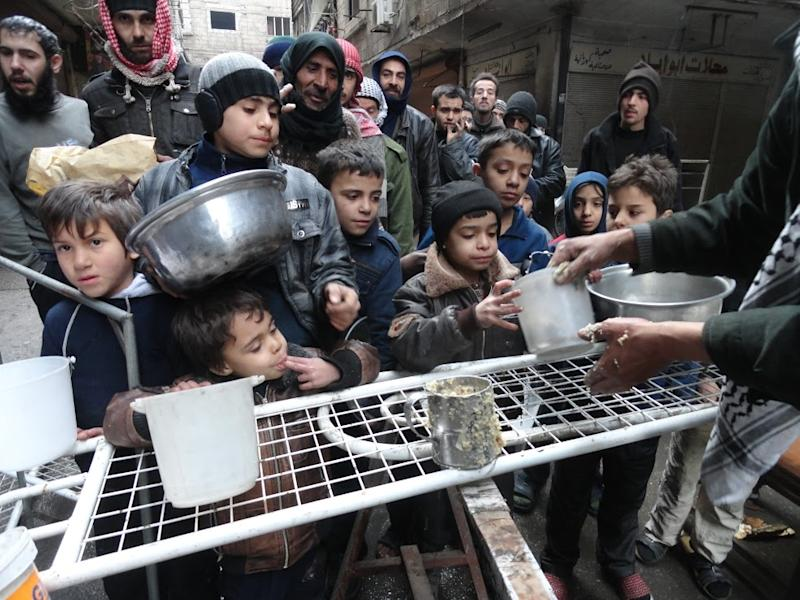 Residents of Syria's besieged Yarmuk Palestinian refugee camp, south of Damascus, gather to collect aid food at the adjacent Jazira neighborhood in February 2015