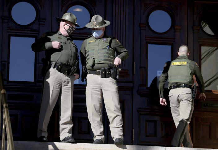 In this Wednesday, Jan. 6, 2021, photo, Wyoming Highway Patrol troopers talk before a Stop the Steal rally outside the Wyoming State Capitol Building in Cheyenne, Wyo. Wyoming Gov. Mark Gordon quietly mobilized dozens of National Guard troops in case of any violence at the state Capitol in Cheyenne in January. The deployment came to light Friday, March 5, 2021, after an Associated Press inquiry after the Jan. 6 riot at the U.S. Capitol, which left five dead. (Michael Cummo/The Wyoming Tribune Eagle via AP)