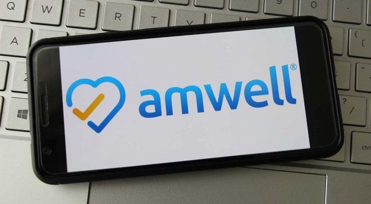 The logo for American Well (AMWL) displayed on a smartphone screen. The smartphone rests on top of a keyboard.