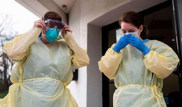 PHOTO: Health care workers from Virginia Hospital Center put on their personal protective equipment before people arrive at a drive-through testing site for the novel coronavirus in Arlington, Virginia, on March 20, 2020. (Andrew Caballero-Reynolds/AFP via Getty Images)