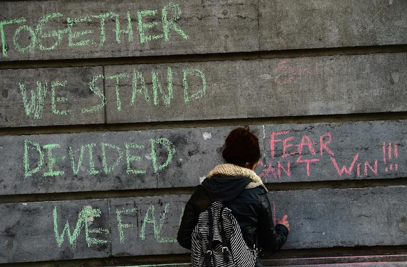 A woman writes a message on a wall as people gather to pay their respects to the victims of terrorist attacks in Brussels (AFP Photo/Emmanuel Dunand)