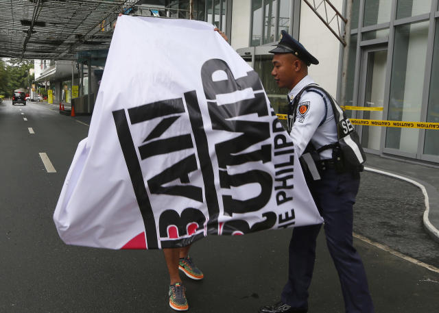 <p>A private guard of Trump Tower prevents a protester from unfurling a banner during a rally to protest the visit of U.S. President Donald Trump, Thursday, Nov. 9, 2017, in the financial district of Makati city, east of Manila, Philippines. (Photo: Bullit Marquez/AP) </p>