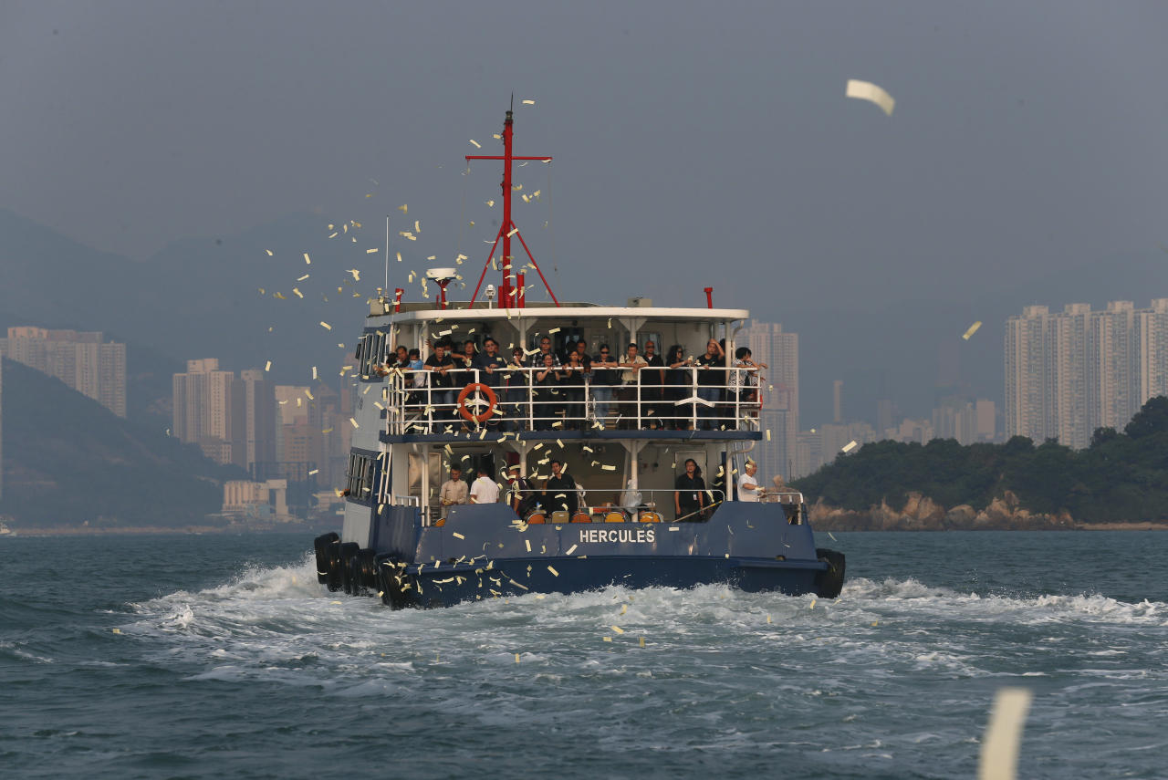 Relatives of victims who died in Monday's ferry collision throw paper money to pay tribute to those lost, Thursday, Oct. 4, 2012, in Hong Kong. A show of concern by Beijing over the boat collision that killed dozens of people in Hong Kong this week has backfired, further damaging the communist government's image in the former British colony. (AP Photo/Kin Cheung)