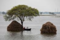 A woman with two children rows small boat in a flooded field in Bhagalpur district