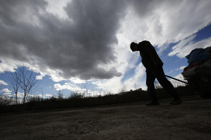 Bosnian man Dzevad Hrustic drags a load found in the garbage close to the coal mine in Bosnian town of Tuzla, 140 kms north of Sarajevo on Wednesday, Feb. 12, 2014. The violence engulfing Bosnia in recent days, with scenes of burning government buildings and protesters pelting police with stones, has many root causes. One of them is the failed privatizations of state-owned companies. (AP Photo/Amel Emric)