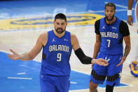 Orlando Magic center Nikola Vucevic (9) and guard Michael Carter-Williams (7) react to a call during the second half of the team's NBA basketball game against the Oklahoma City Thunder, Tuesday, Dec. 29, 2020, in Oklahoma City. (AP Photo/Sue Ogrocki)