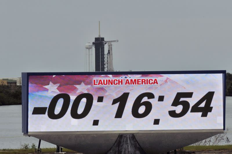 A screen showing the countdown clock is seen with SpaceX Falcon 9 rocket and Crew Dragon spacecraft in the background as launch from NASA's Kennedy Space Center was scrubbed, in Cape Canaveral