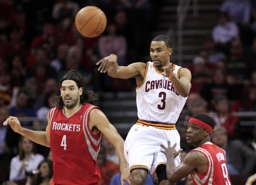 Cleveland Cavaliers' Ramon Sessions (3) passes in front of Houston Rockets' Luis Scola (4), from Argentina, and Jonny Flynn (9) in the first quarter in an NBA basketball game Sunday, March 11, 2012, in Cleveland. (AP Photo/Tony Dejak)