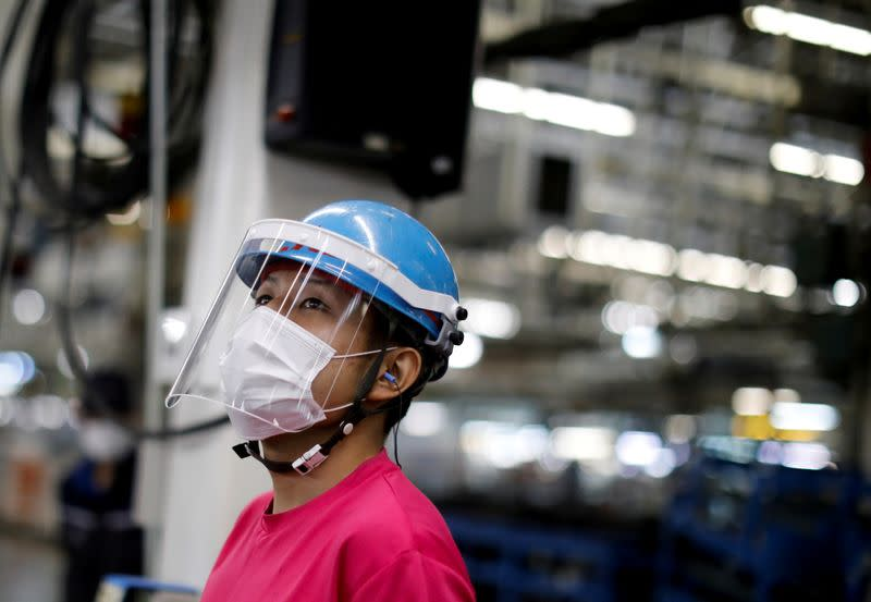 FILE PHOTO: An employee wearing a protective face mask and face guard works on the automobile assembly line during the outbreak of the coronavirus disease (COVID-19) at the factory of Mitsubishi Fuso Truck and Bus Corp. in Kawasaki