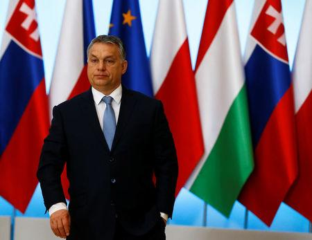 Visegrad Group member nation Hungary's PM Orban stands after a news conference during a summit in Warsaw