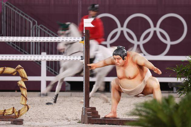 A show jumper rides behind an obstacle with a sumo wrestler beside it in an event at the Tokyo Olympics. (Photo: picture alliance via Getty Images)