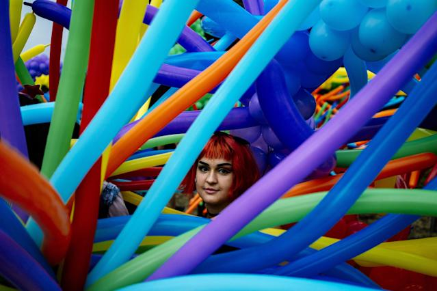 <p>A participant looks through balloons during the 11th Gay Pride Parade in downtown Sofia on June 9, 2018, as gays, lesbians and transsexuals march through Bulgarian capital to protest against discrimination against homosexuals and improve their integration in the society. (Photo: Dimitar Dilkoff/AFP/Getty Images) </p>